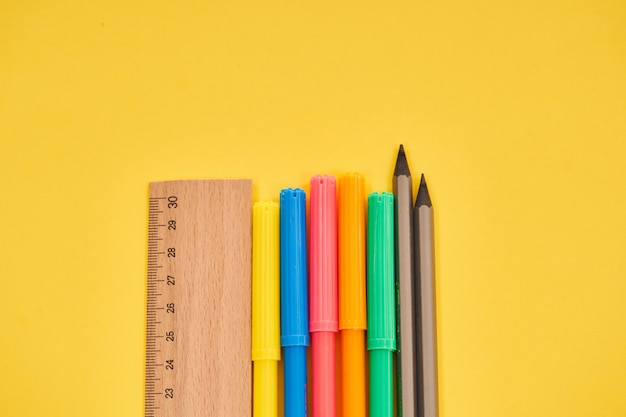 Règle avec des crayons et des stylos colorés sur fond jaune