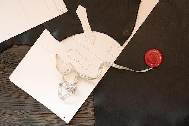 La règle en cuir et les dessins sont placés sur la table