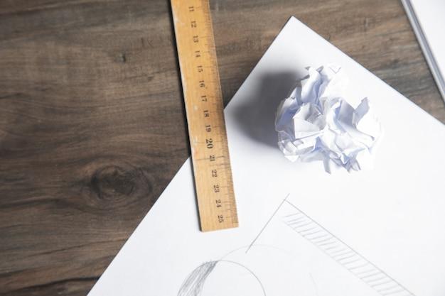Une règle et du papier froissé sur la table