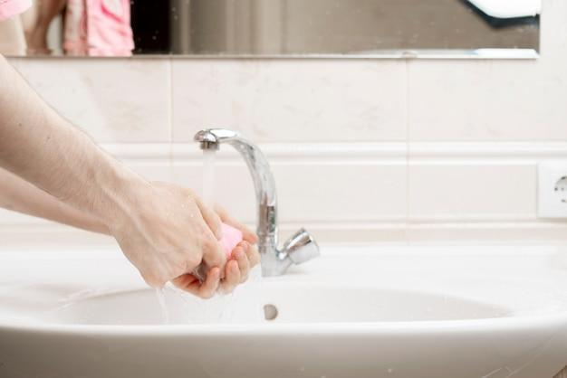 Règles d'hygiène personnelle, personne avec un morceau de brique de savon et se laver les mains sales, protection contre le coronavirus