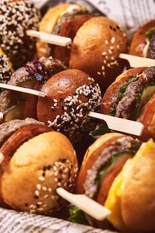 Réglez les hamburgers avec du poisson, de la viande et des légumes. vue de dessus. espace libre pour votre texte. sur un fond en bois.