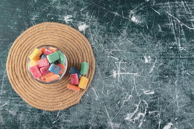 Réglisse colorée dans un bol en verre rond placé sur fond de marbre.