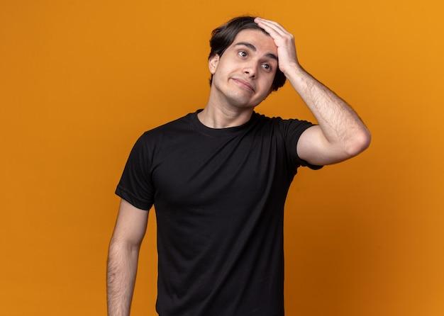 Regretté jeune beau mec portant un t-shirt noir mettant la main sur le front isolé sur le mur orange