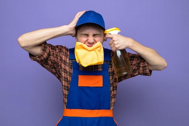 Regretté de mettre la main sur la tête avec les yeux fermés jeune homme de ménage en uniforme et casquette mettant un chiffon dans la bouche tenant un agent de nettoyage sur la tête
