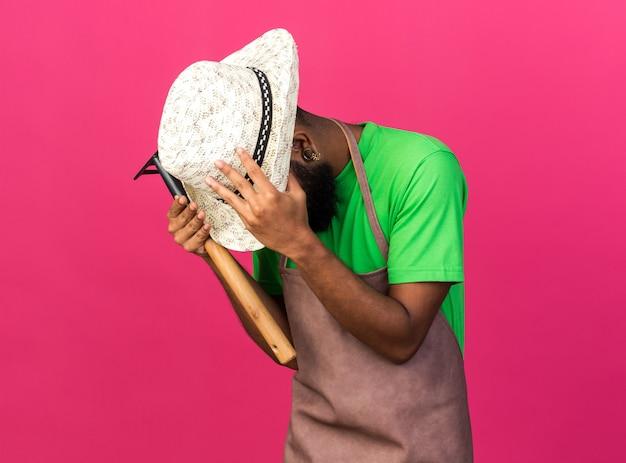 Regretté avec la tête baissée jeune jardinier afro-américain portant un chapeau de jardinage tenant un râteau attrapé la tête