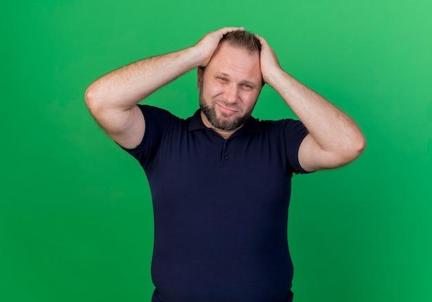 Regretter l'homme slave adulte mettant les mains sur la tête à la recherche d'isolement sur le mur vert