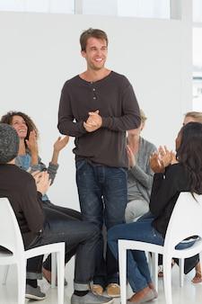 Rehab groupe applaudissant heureux homme debout