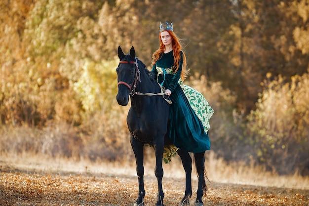 Reine aux cheveux rouges dans une robe verte avec une couronne sur un cheval