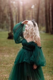 Reine de belle jeune femme cheveux blonds. princesse marche. automne forêt verte mystique. couronne brillante médiévale vintage.
