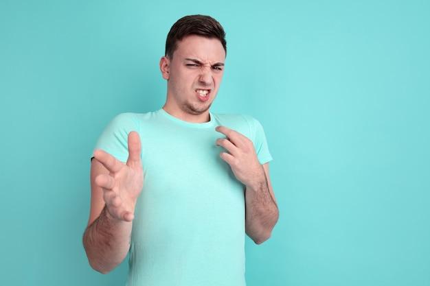 Rejetant, dégoûté. portrait de jeune homme caucasien isolé sur mur bleu. beau modèle masculin dans un style décontracté, couleurs pastel. concept d'émotions humaines, expression faciale