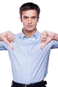 Rejeté! jeune homme sérieux en chemise bleue montrant ses pouces vers le bas et regardant la caméra en se tenant debout isolé sur blanc