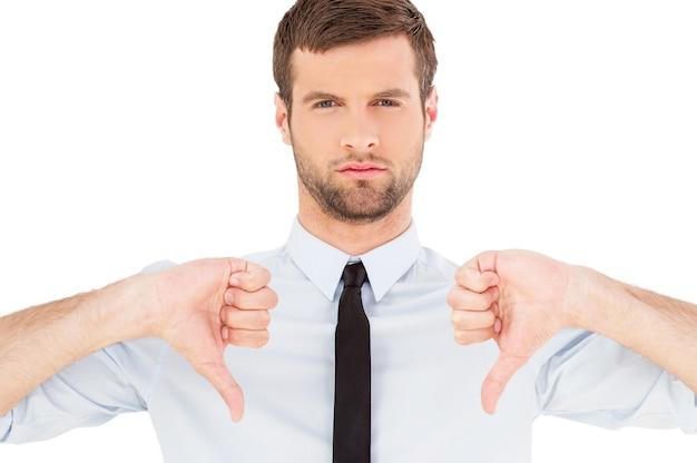 Rejeté! portrait d'un jeune homme confiant en chemise et cravate regardant la caméra et montrant ses pouces vers le bas tout en se tenant isolé sur fond blanc
