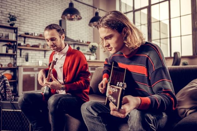 Rejoindre un ami. musicien aux cheveux blonds avec coupe bob rejoignant son ami jouant de la guitare à la maison