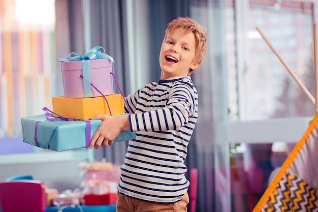 Rejoins moi. joyeux enfant blond se sentant le bonheur tout en ayant une fête d'anniversaire