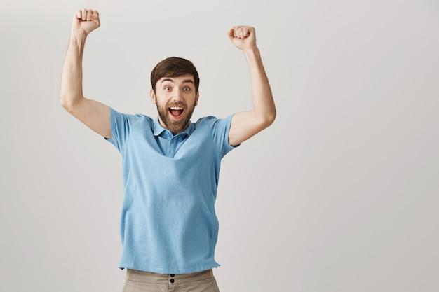 Réjouissant heureux jeune homme barbu posant