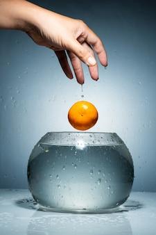 Relâchez une orange de la main dans le bocal à poisson avec des éclaboussures d'eau.