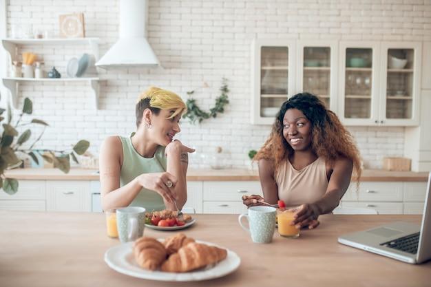 Relation. couple de jeunes copines heureux adultes assis s'amuser à parler tout en prenant le petit déjeuner à la maison