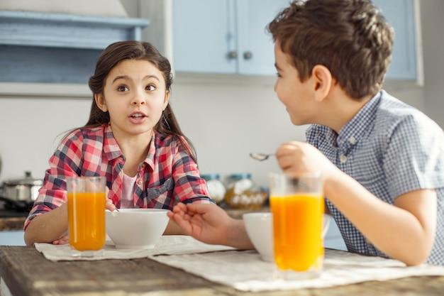Relation. jolie petite fille brune aux cheveux noirs qui parle avec son frère pendant qu'ils prennent leur petit-déjeuner et boivent du jus