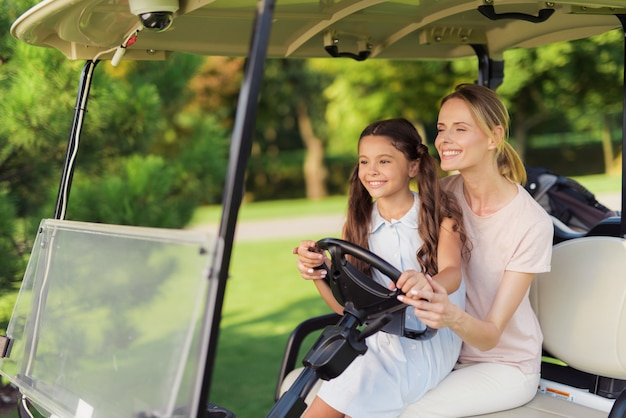 Relations familiales golfers drive golf car caddy.