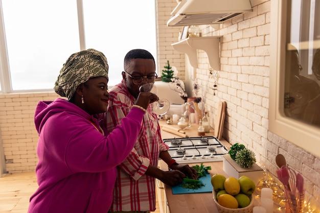 Relations de famille. belle femme afro-américaine debout avec son mari tout en essuyant son visage avec une serviette