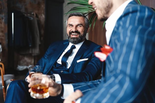 Relaxant. sur toute la longueur de deux jeunes hommes beaux en costumes tenant des lunettes et se regardant tout en se reposant à l'intérieur.