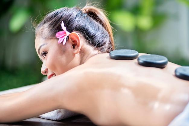 Relaxante femme asiatique profitant d'un massage aux pierres chaudes