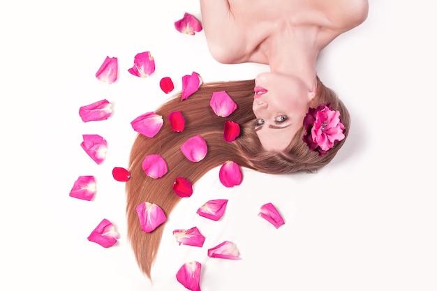 Relaxarea belle fille, allongée parmi les pétales de rose. soins de la peau et concept de mode de vie sain