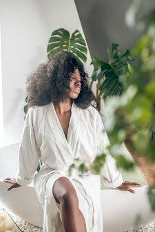Relaxation. jeune femme afro-américaine pensive détendue en peignoir assis sur une baignoire blanche dans un salon spa