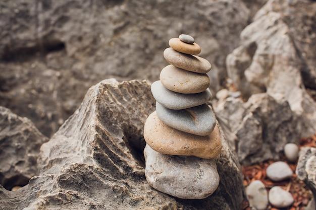 Relaxation de méditation zen - image de style hipster filtré effet rétro vintage de pile de pierres équilibrées avec fleur de frangipanier plumeria bouchent sur la plage de la mer.