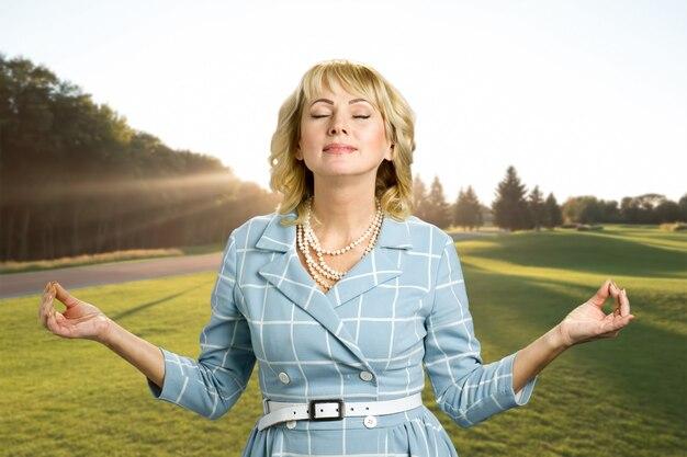 Relaxation zen magnifique femme mûre. femme blonde d'âge moyen pratiquant la méditation avec les yeux fermés sur la nature.
