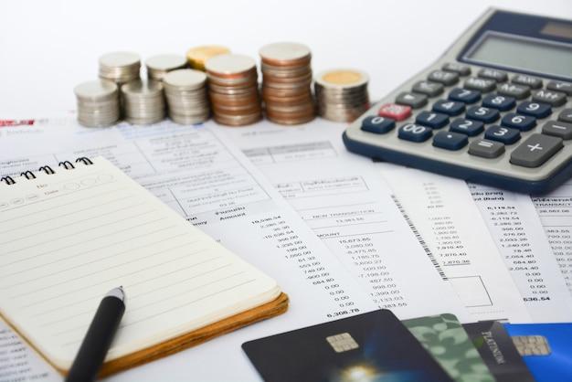 Relevés de carte de crédit, stylo, carnet, pièces de monnaie et calculatrice sur fond blanc