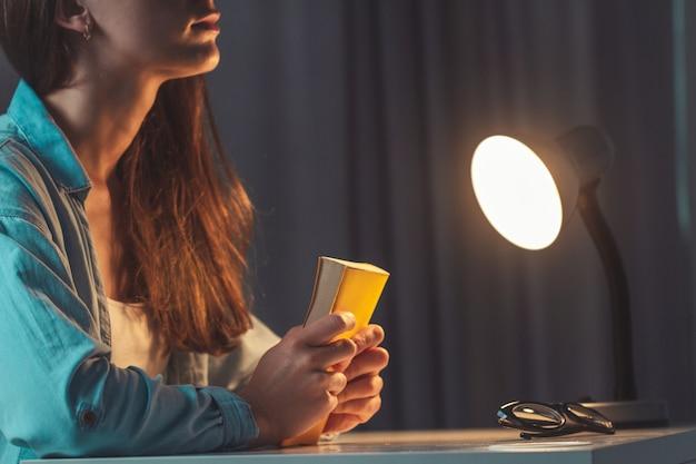 Religion femme priant avec la bible le soir à la maison et se tourner vers dieu, demander pardon et croire en la bonté