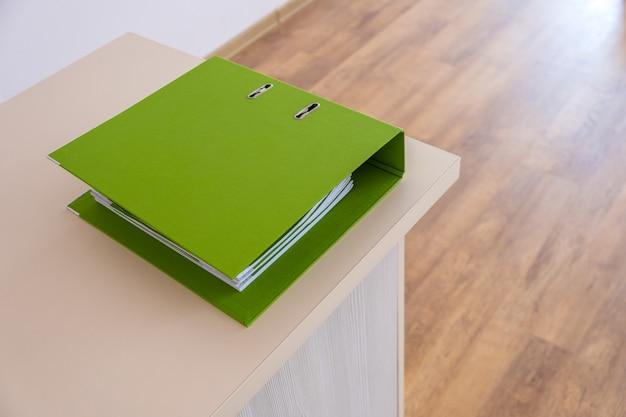Reliure verte avec des documents de bureau sur une table de travail.