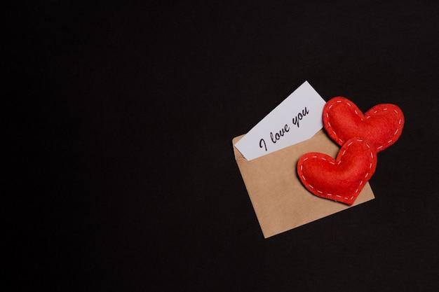 Remarque je t'aime dans une enveloppe avec deux coeurs sur fond noir