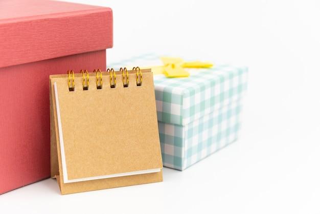 Remarque papier ou calendrier avec deux coffret cadeau sur fond blanc. concept de cadeau.