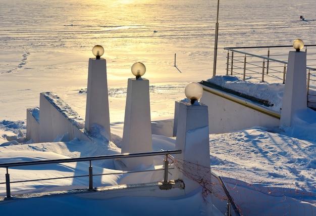 Remblai d'hiver au coucher du soleil le parapet de l'escalier avec des poteaux d'éclairage