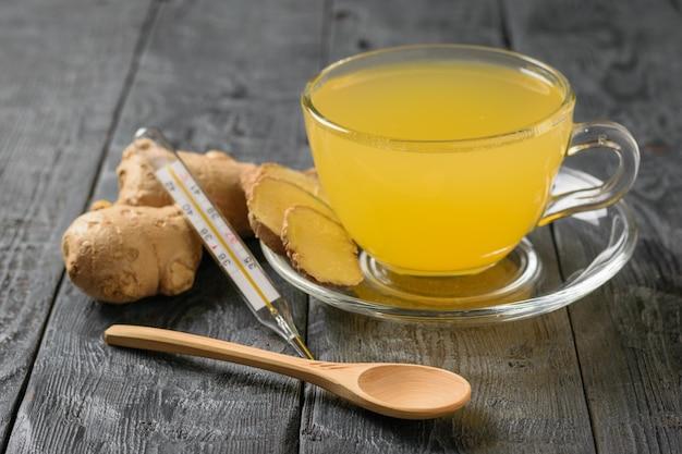 Remède contre le rhume à base de gingembre et d'agrumes dans un bol en verre posé sur la table.