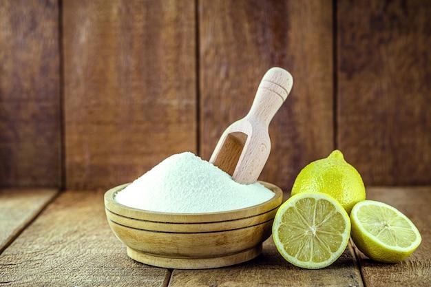 Remède maison contre l'acide gastrique, bol avec du bicarbonate de soude et des agrumes comme le citron ou l'orange autour