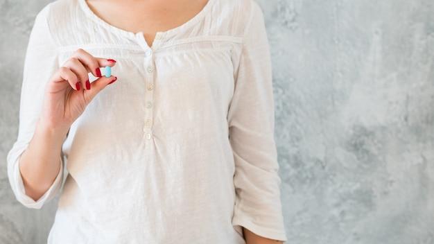 Remède universel. pilule magique pour guérir toutes les maladies. femme tenant la capsule à la main.