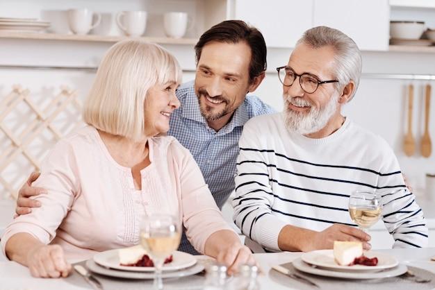 Remerciant mes parents pour tout. sourire prudent bel homme en train de dîner et de passer du temps avec ses parents aînés tout en leur exprimant leur amour