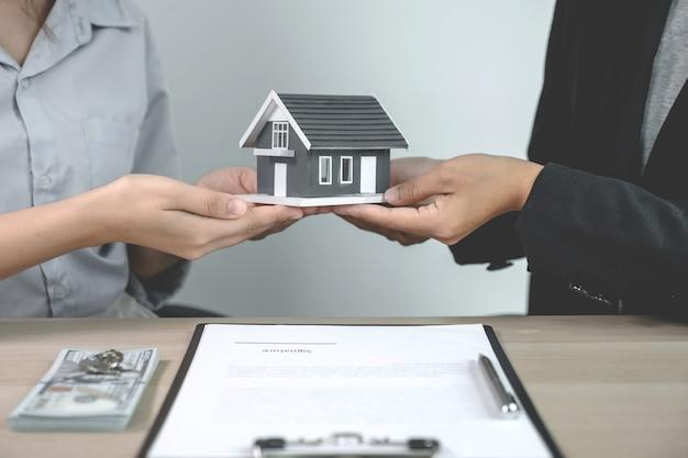 Remettez un agent immobilier, tenez le modèle de maison et expliquez le contrat commercial,