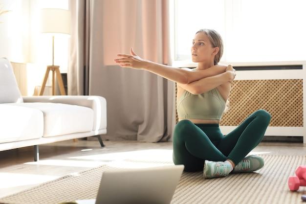 Remise en forme belle femme mince faisant des exercices d'étirement de remise en forme à la maison dans le salon. restez à la maison activités. sport, mode de vie sain.