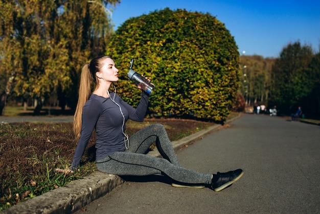 Remise en forme dans le parc, fille assise l'eau potable.