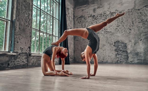 Remise en forme, étirements, groupe de deux femmes séduisantes faisant du yoga. notion de bien-être. yoga partenaire. équilibre, concentration, concept d'équilibre.