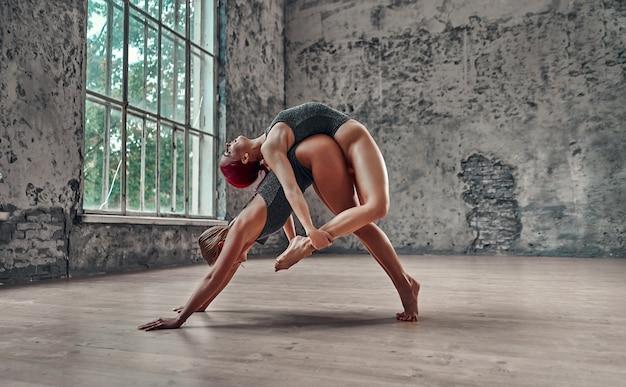 Remise en forme, étirements, groupe de deux femmes séduisantes faisant du yoga. pose du chien + pose de l'arc. notion de bien-être.