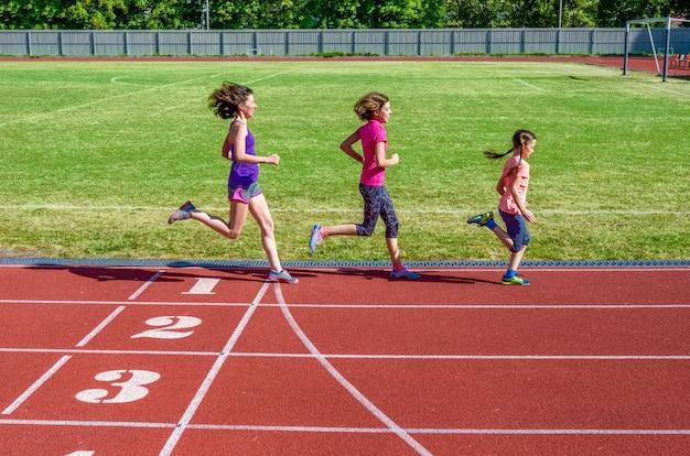 Remise en forme familiale, mère et enfants en cours d'exécution sur la piste du stade, formation et enfants sport concept de mode de vie sain