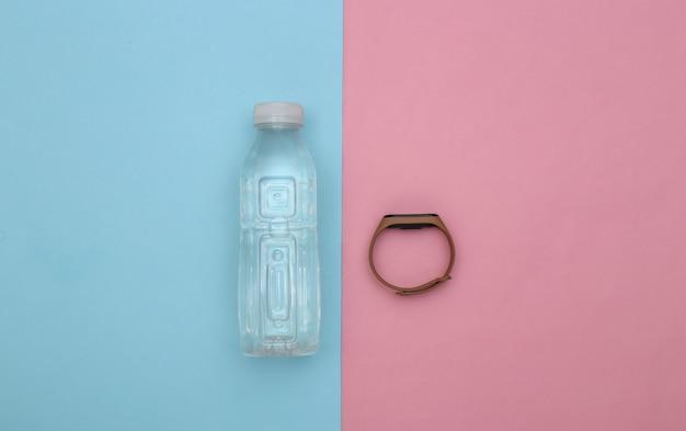 Remise en forme, sport minimaliste à plat. bouteille d'eau et bracelet intelligent sur fond bleu-rose. vue de dessus