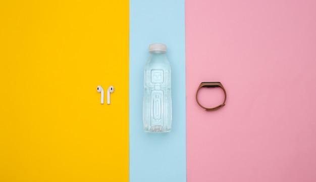 Remise en forme, sport minimaliste à plat. bouteille d'eau, écouteurs sans fil et bracelet intelligent sur fond bleu-rose. vue de dessus