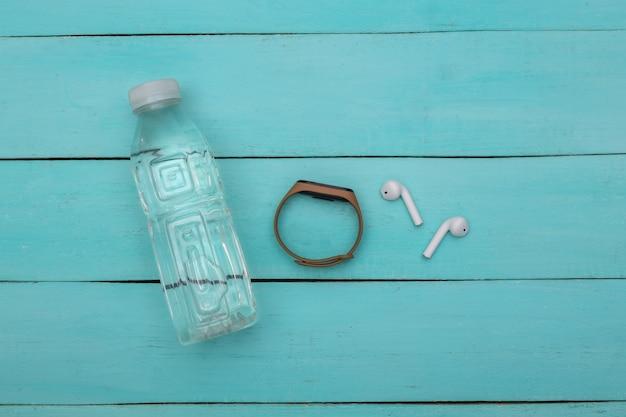 Remise en forme, sport minimaliste à plat. bouteille d'eau, écouteurs sans fil et bracelet intelligent sur fond de bois bleu. vue de dessus