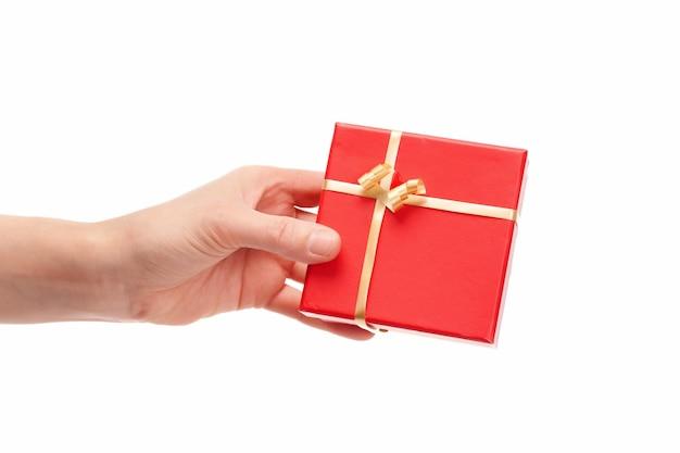 Remise de la main sur un cadeau sur fond blanc, espace copie